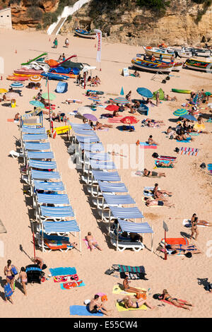 People sunbathing on a beach on holiday, Carvoeiro, the Algarve, Portugal, Europe - Stock Photo