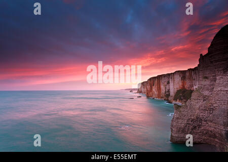 fire sunrise over cliffs in Atlantic ocean, France - Stock Photo