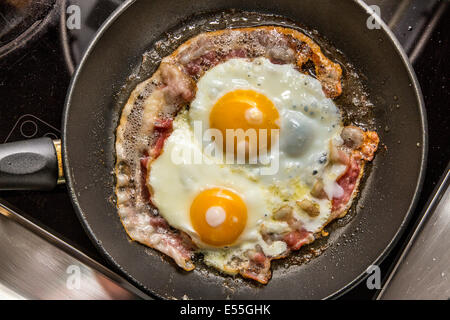 Fried eggs and bacon in a frying pan, breakfast, - Stock Photo