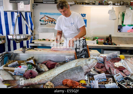 A fishmonger fillets fish at the Saturday morning Market in Chamonix, Haute Savoie, France. - Stock Photo