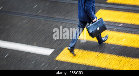 Man rushing over a road crossing in a city on a rainy day (motion blurred image) - Stock Photo