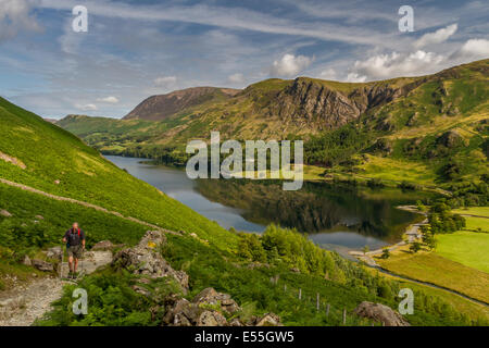 Walker ascending mountain path to Scarth Gap from Buttermere in the English Lake District - Stock Photo