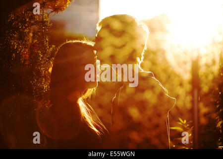 Young couple in love kissing in backlight - Stock Photo