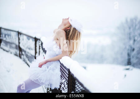Ballerina leaning on the fence in snow - Stock Photo