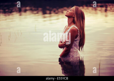 Young woman in white dress standing in water - Stock Photo