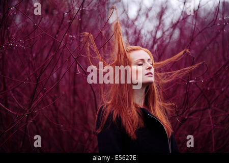 Woman with long red hair between branches, portrait - Stock Photo