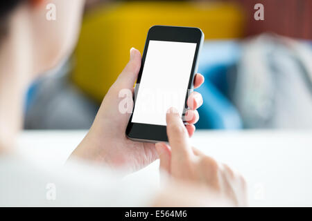Woman with modern mobile phone in hands touching on a blank screen. Blurred office interior on a background. - Stock Photo