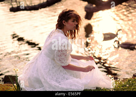 Young woman in white dress sitting by the lake - Stock Photo