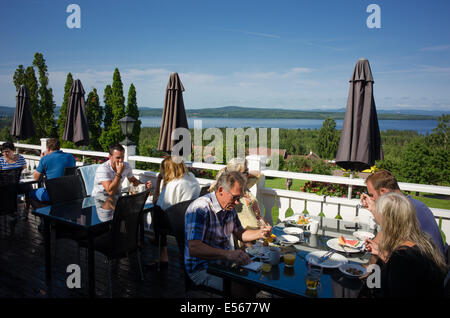 Tourists enjoy breakfast on a quiet summer morning at Lake Siljan in the Swedish folklore district Dalecarlia - Stock Photo