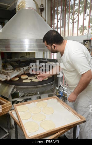 Pita Bakery. The baker removes the pita from the oven - Stock Photo