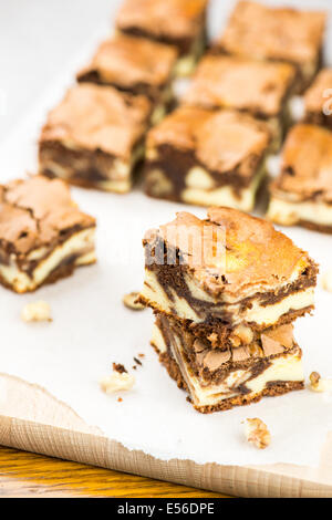 Sweet brownies stacked on white paper and wood - Stock Photo