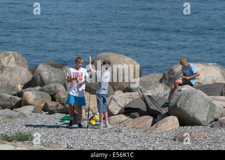 Teenage boys enjoying their summer holidays angling in the Sound, Øresund, from the Kronborg point at Helsingør - Stock Photo