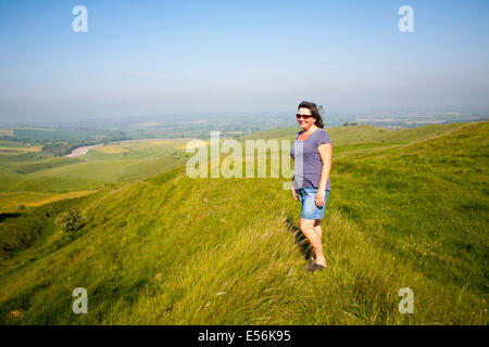 Woman standing on steep chalk scarp slope on downland at Cherhill Down, Wiltshire, England - Stock Photo