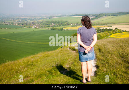Woman standing on steep chalk scarp slope  Cherhill Down, Wiltshire, England looking towards the village of Cherhill - Stock Photo