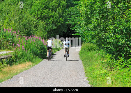 Cyclists on the Monsal Trail in Upperdale, Derbyshire, Peak District National Park, England, UK. - Stock Photo