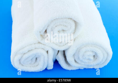 Three large white cotton bath cloths rolled up individually and piled together on a blue background. A few white - Stock Photo
