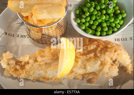 Deep fried fish (Haddock) and chips with garden peas and a segment of lemon on a fake newspaper style backing paper. - Stock Photo