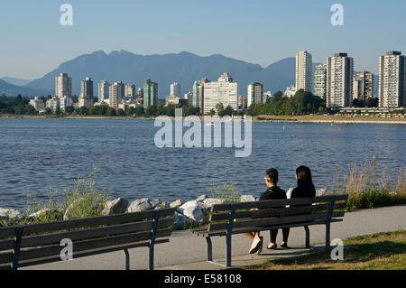 Young Asian couple on a bench overlooking English Bay with West End skyline and North Shore mountains in background, - Stock Photo