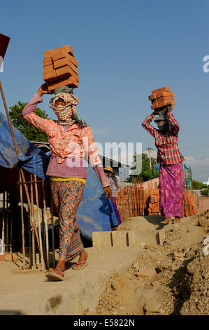 Female construction workers carry bricks on their heads, high rise construction site, Mandalay, Myanmar - Stock Photo