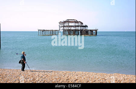 Brighton, Sussex, UK. 23rd July, 2014. A man with a metal detector takes in the view by the West Pier on Brighton - Stock Photo