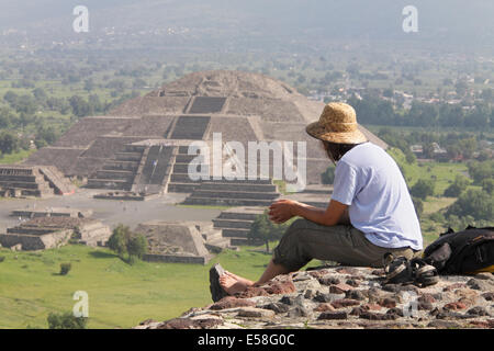 A tourist atop the Pyramid of the Sun gazes at the Pyramid of the Moon in the distance, Teotihuacan, Mexico. - Stock Photo