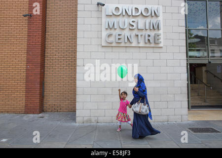 Islamic woman and child pass by the London Muslim Centre, East London Mosque on Whitechapel Road, - Stock Photo