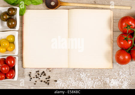 Vintage book and paper with text space for ingredients of a recipe on a wooden table - Stock Photo