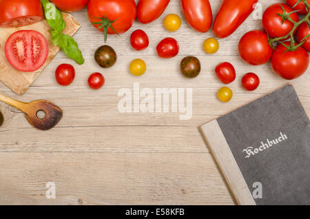 Different tomatoes with wooden spoon and recipe book on a old wooden board - Stock Photo