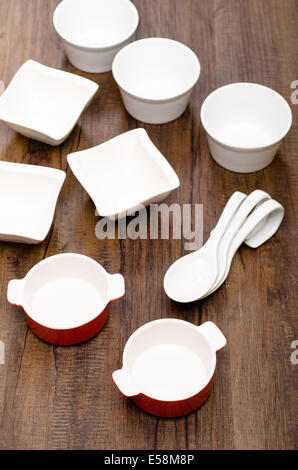Different china bowls on wooden table - Stock Photo