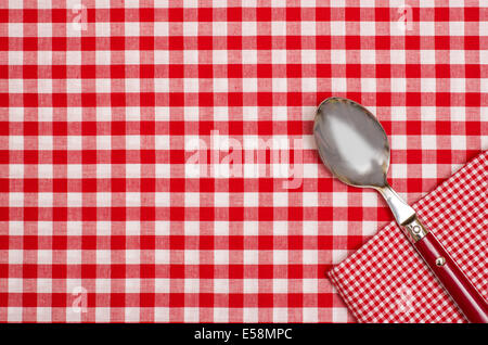 red silverware on a red checkered napkin and table cloth stock photo