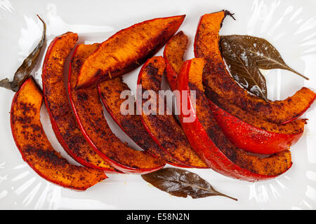 Roasted pumpkin slices served on white plate from above close up - Stock Photo