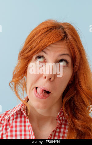 Hipster girl making funny faces, tongue out, looking up - Stock Photo