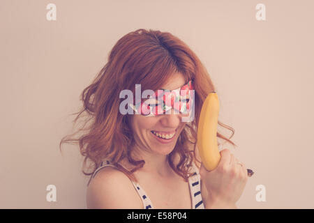 Superhero hipster girl wearing mask with strawberries, holding a banana gun - Stock Photo