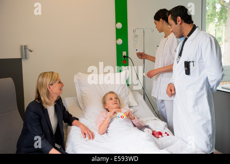 Male doctor attending to a girl patient in hospital bed - Stock Photo