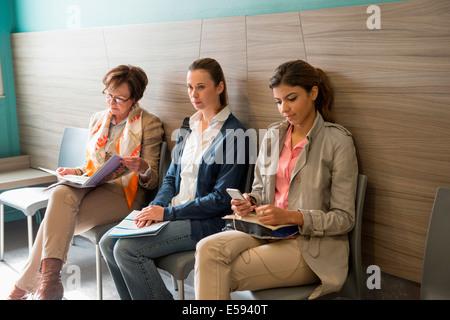 Three women in waiting area of hospital - Stock Photo