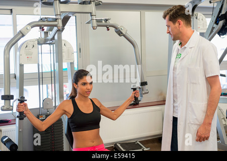 Male instructor guiding a woman in exercising - Stock Photo