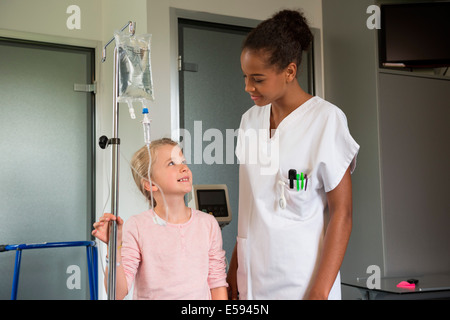 Female nurse assisting to a girl patient in hospital - Stock Photo