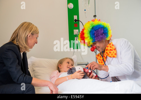 Male doctor wearing clown costume making girl patient smile in hospital bed - Stock Photo