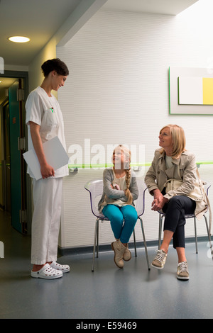 Female nurse talking with patients in waiting room - Stock Photo