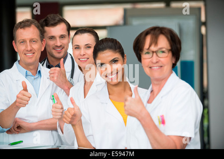 Portrait of medical-team showing thumbs up - Stock Photo