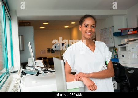 Portrait of a female nurse smiling in nurses office - Stock Photo