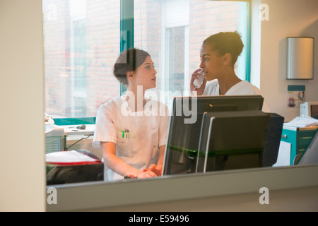 Two female nurses working in office - Stock Photo