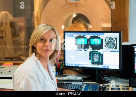 Female doctor examining brain MRI scan on computer - Stock Photo