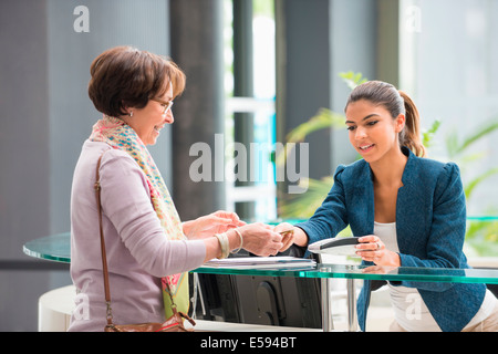 Woman making payment with credit card at reception desk - Stock Photo
