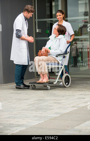 Male doctor talking to a female patient sitting in a chair - Stock Photo