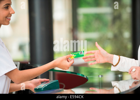 Woman giving french social security card to receptionist at hospital reception desk - Stock Photo