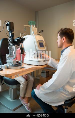 Male optometrist examining woman's eyes - Stock Photo