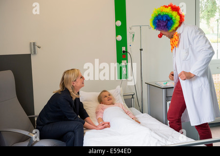 Male doctor wearing clown costume making girl patient laugh in hospital bed - Stock Photo