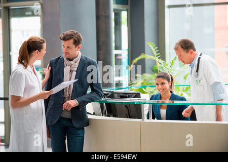 Female doctor discussing with patient at hospital reception desk - Stock Photo