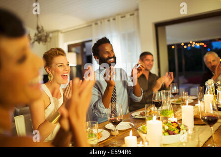 Friends cheering at dinner party - Stock Photo